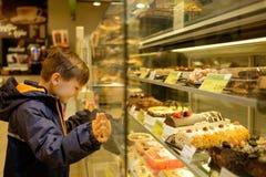Weinig jongen dichtbij vertoning met cakes Royalty-vrije Stock Afbeelding