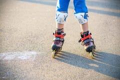 Weinig jongen die aan rolschaats in de zomerpark leren Kinderenwea royalty-vrije stock fotografie