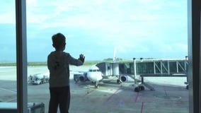 Weinig jongen die aan venster het wachten vliegtuig in vertrekzitkamer kijken in luchthaven Jonge jongen die aan vliegtuigen van  stock videobeelden