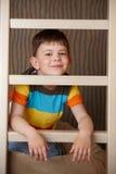 Weinig jongen die achter ladder het glimlachen speelt stock foto
