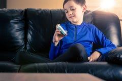 Weinig jongen die astmainhaleertoestel bekijken royalty-vrije stock afbeelding