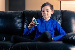 Weinig jongen die astmainhaleertoestel bekijken stock foto