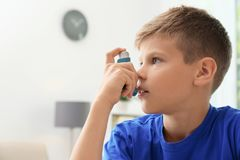 Weinig jongen die astmainhaleertoestel met behulp van stock fotografie