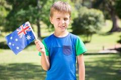 Weinig jongen die Australische vlag golven Stock Foto