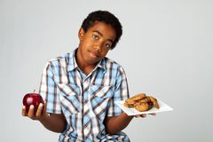 Weinig jongen die besluiten van het eten van gezonde ongezonde verzen nemen royalty-vrije stock afbeeldingen