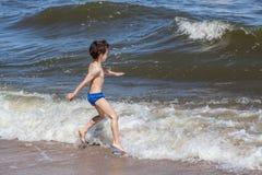 Weinig jongen die bij de kust spelen royalty-vrije stock afbeelding