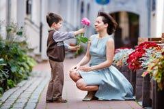 Weinig jongen die bloem geven aan zijn mamma Stock Foto's