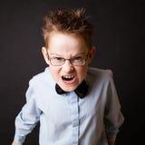 Weinig jongen die boos gezicht maken stock afbeelding