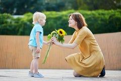 Weinig jongen die bos van zonnebloemen aanbieden aan zijn mamma stock afbeelding