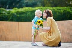 Weinig jongen die bos van zonnebloemen aanbieden aan zijn mamma royalty-vrije stock afbeelding