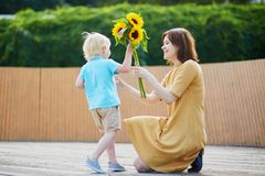 Weinig jongen die bos van zonnebloemen aanbieden aan zijn mamma royalty-vrije stock foto's