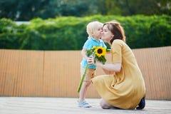 Weinig jongen die bos van zonnebloemen aanbieden aan zijn mamma stock foto