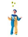 Weinig jongen die in clownkostuum met drie ballen en het glimlachen jongleren Royalty-vrije Stock Afbeelding