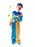 Weinig jongen die in clownkostuum met drie ballen en het glimlachen jongleren Stock Afbeeldingen