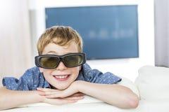 Weinig jongen die 3D glazen dragen en op televisie letten Stock Foto's