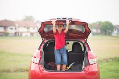 Weinig jongen die de auto van de achterdeurauto sluiten stock afbeelding