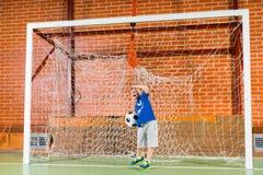 Weinig jongen die in de doelstellingen bij voetbal spelen royalty-vrije stock foto's