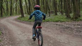 Weinig jongen die de fiets in het bos berijden bij park stock footage