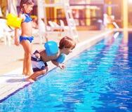 Weinig jongen die in de pool springen Stock Fotografie