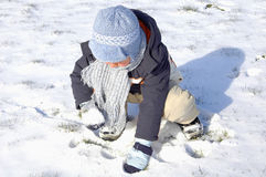 Weinig jongen die in de sneeuw speelt Stock Foto's