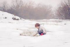 Weinig jongen die in de sneeuw speelt Royalty-vrije Stock Fotografie