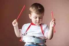 Weinig jongen die de trommel spelen het concept van de kindontwikkeling royalty-vrije stock fotografie