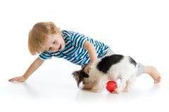Weinig jongen die die met hond spelen, op witte achtergrond wordt geïsoleerd Stock Foto