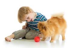 Weinig jongen die die met hond spelen, op witte achtergrond wordt geïsoleerd Stock Afbeeldingen