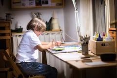 Weinig jongen die in donkere ruimte laat in de avond schilderen Royalty-vrije Stock Foto's
