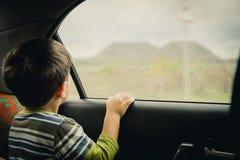 Weinig jongen die door venster kijken Stock Foto
