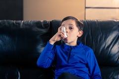 Weinig jongen die een astmainhaleertoestel binnen met behulp van royalty-vrije stock foto's