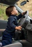 Weinig jongen die een auto drijft Stock Foto