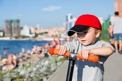 Weinig jongen die een autoped berijden op dijk in Vladivostok stock afbeeldingen