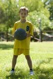 Weinig jongen die een basketbal houdt Royalty-vrije Stock Foto's