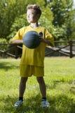 Weinig jongen die een basketbal houdt Stock Afbeeldingen