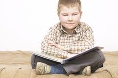 Weinig jongen die een boek leest stock fotografie