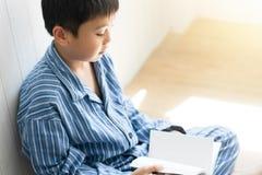 Weinig jongen die een boek lezen bij slaapkamer stock foto's