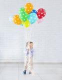 Weinig jongen die een bos van gekleurde ballons houden Royalty-vrije Stock Fotografie