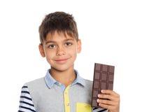 Weinig jongen die een chocolade houden Stock Afbeeldingen