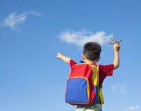 Weinig jongen die een een vliegtuigstuk speelgoed en punt houden Stock Foto's