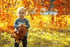 Weinig jongen die een gevuld stuk speelgoed in het park in openlucht in de herfst houden Stock Afbeelding