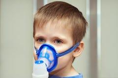 Weinig jongen die een inhaleertoestel met behulp van stock afbeelding