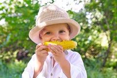 Weinig jongen die een maïskolf van gekookt graan eten royalty-vrije stock foto