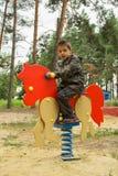 Weinig jongen die een oranje paard berijden bij de speelplaats Stock Afbeeldingen