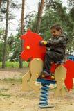 Weinig jongen die een oranje paard berijden bij de speelplaats Royalty-vrije Stock Afbeelding