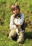 Weinig jongen die een puppy houden royalty-vrije stock afbeelding