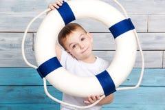 Weinig jongen die een reddingsboei en lach houden Royalty-vrije Stock Fotografie