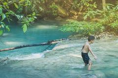 Weinig jongen die een rivierhoogtepunt van stenen kruisen zorgvuldig en in waterval bij het Nationale Park van Erawan wankelen stock fotografie