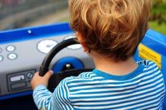 Weinig jongen die een stuk speelgoed auto drijft stock fotografie