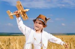 Weinig jongen die een stuk speelgoed vliegtuig op een tarwegebied vliegen Royalty-vrije Stock Foto's